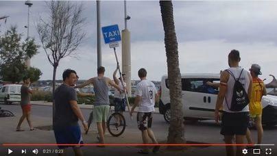 Un grupo de turistas pasean un poste de taxis por S'Arenal
