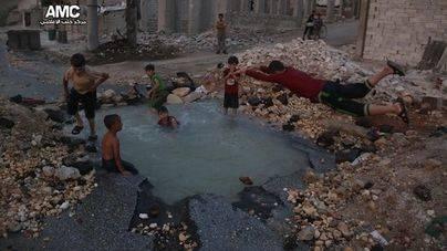 Un grupo de niños sirios usan como piscina el cráter de una bomba
