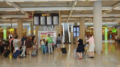 Pasajeros ante el panel de información del aeropuerto de Palma