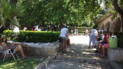 Turistas a la sombra este viernes en S'Hort del Rei de Palma (Foto: Cristina Suárez)