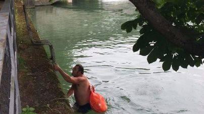 Nadando por el río con su traje, ordenador y zapatos para ir a trabajar