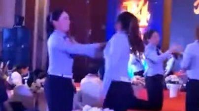 Empleadas de una compañía china, obligadas a pegarse por parejas