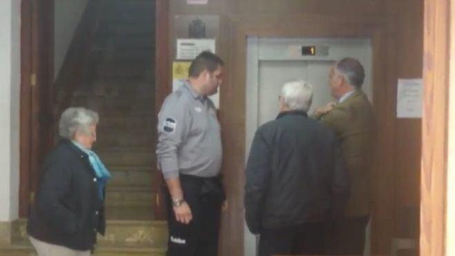 El anciano, de espaldas, y su mujer a la entrada del juzgado