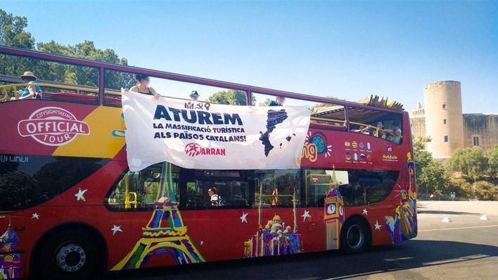 Arran arremete contra un bus con botes de humo y pancartas por 'la masificación en los Països Catalans'