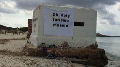 Cuelgan unas pancartas contra el turismo masivo en la playa de Ses Covetes