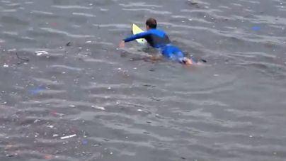 Un surfero surca las aguas contaminadas de Palma