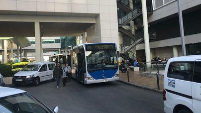 Autobuses, en cola para circular por el recinto lleno de coches mal aparcados