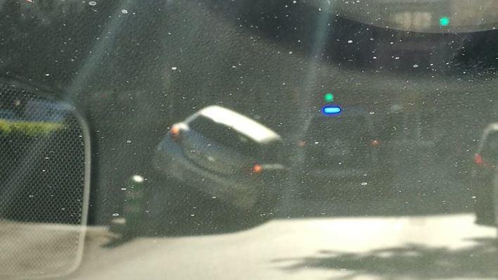 Atasco en Avenidas tras el accidente de un coche que quedó subido en el muro de un parking