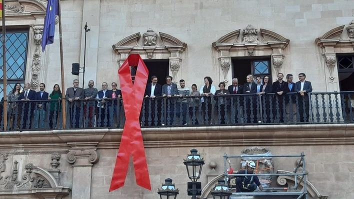 Cort cuelga un lazo rojo por la lucha contra el estigma del SIDA