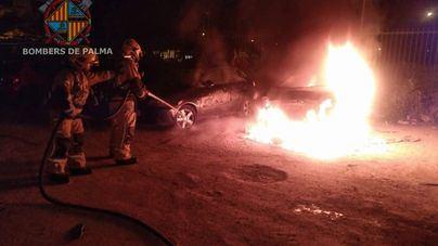 Arden dos coches en un parking en Can Capas