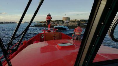 Remolcan un velero encallado en una zona rocosa de Menorca