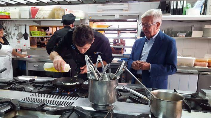 Rafael Ansón observa la elaboración de un plato durante una visita a la isla